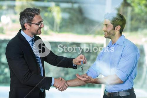 Estate agent giving resort key to man