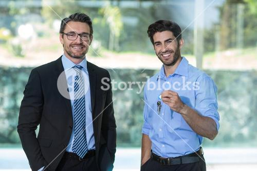 Man standing with real estate agent holding a house key