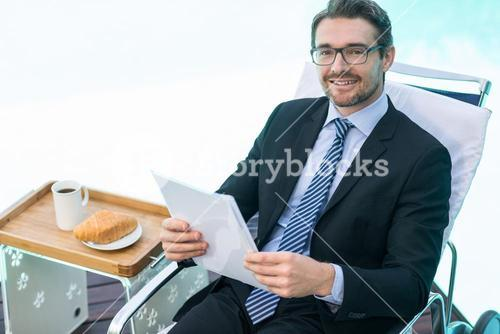 Smart man holding document near pool