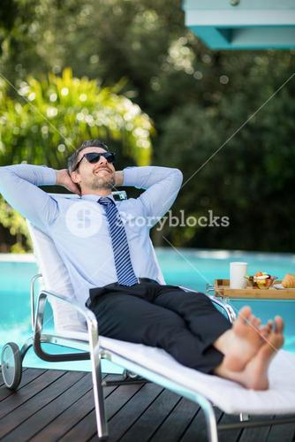 Smart man relaxing on sun lounger