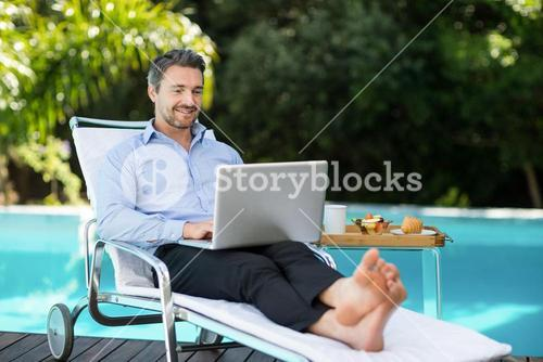 Smart man using laptop near pool