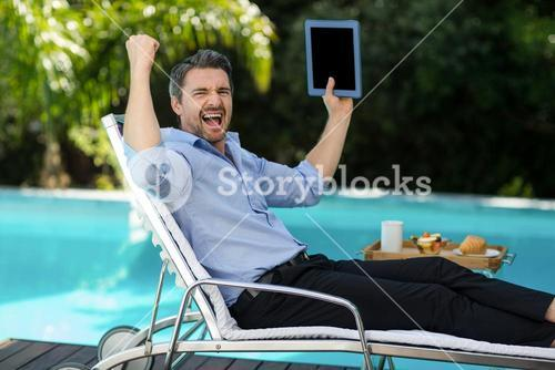 Excited man holding a digital tablet near pool