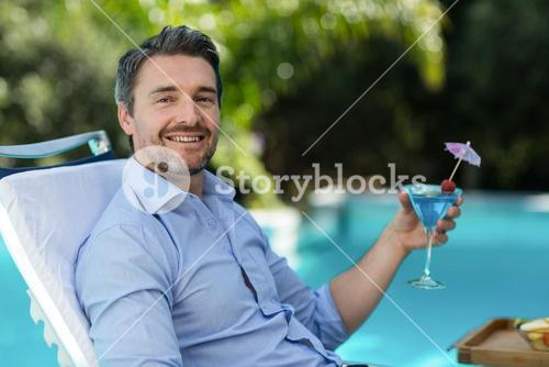 Smart man holding martini glass while relaxing in sun lounger
