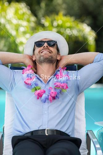 Smart man wearing garland while relaxing in sun lounger