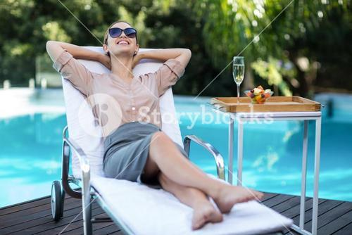 Happy businesswoman relaxing in sun lounger