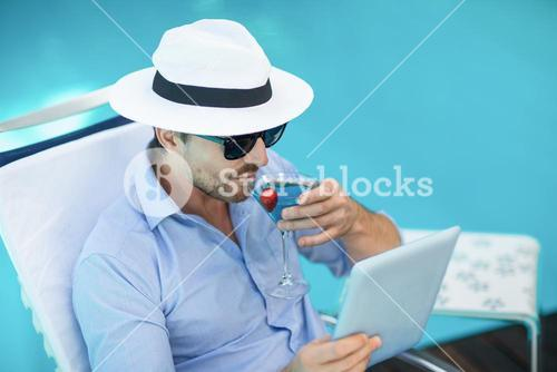 Smart man having martini while using digital tablet near pool