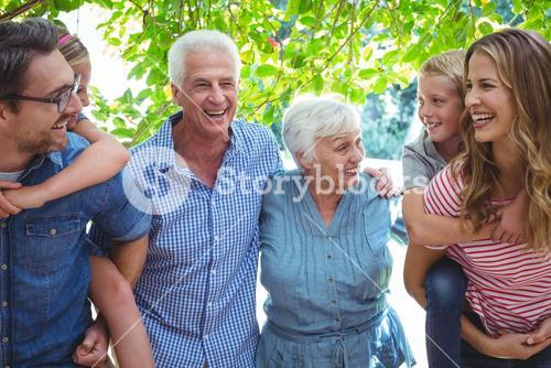 Cheerful multi generation family with parents giving piggy back