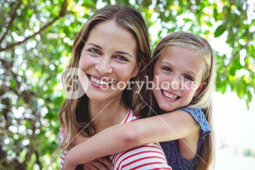 Smiling mother giving piggy-back to daughter