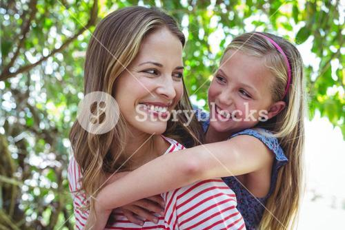 Happy mother giving piggy-back to daughter