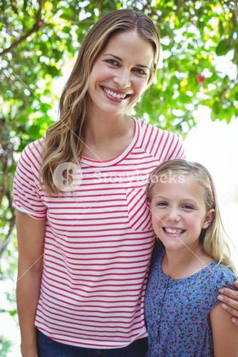 Smiling mother and daughter with arm around