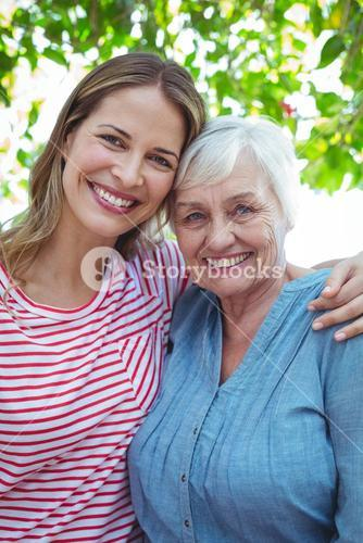 Portrait of happy mother and daughter with arm around