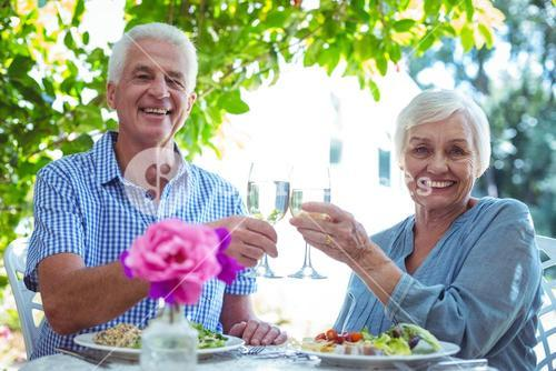 Smiling senior couple toasting white wine