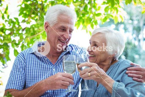 Retired couple toasting white wine