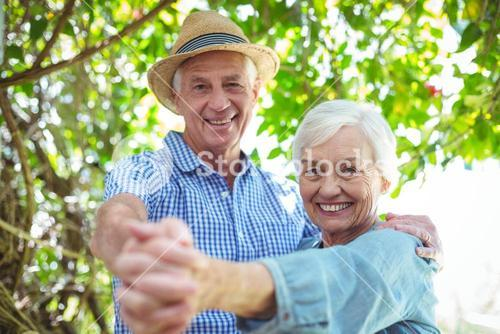 Cheerful retired couple dancing outdoors