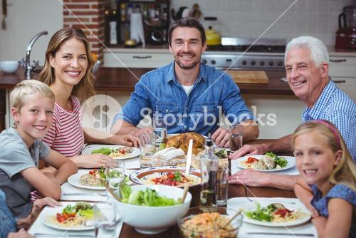 Smiling multi generation family sitting at dining table
