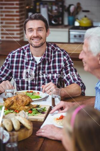 Smiling father sitting at dining table