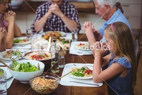 Multi generation family praying with granddad sitting at dining table