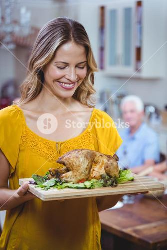 Smiling woman holding cutting board with meat