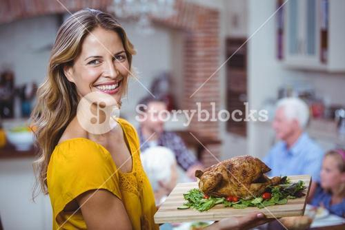 Portrait of smiling woman holding cutting board with meat