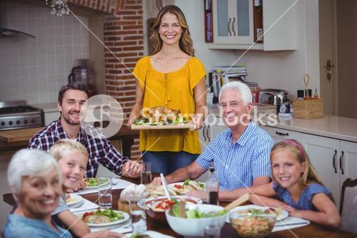 Smiling family at dining table with mother standing