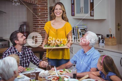 Happy family at dining table with mother