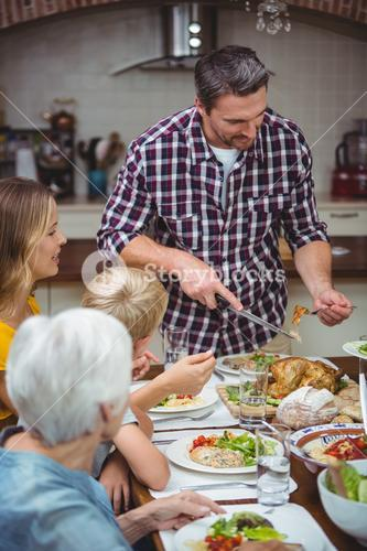 Father serving food while standing at dining table