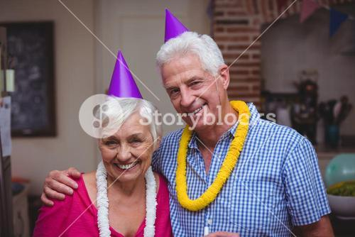 Smiling senior couple wearing party hat