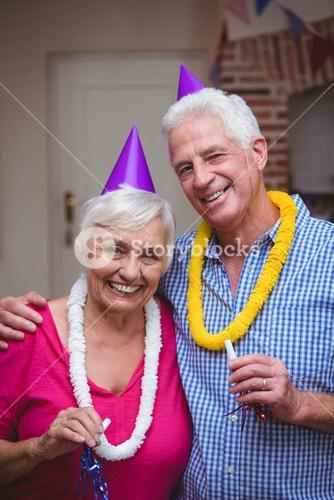 Portrait of smiling senior couple holding party horn
