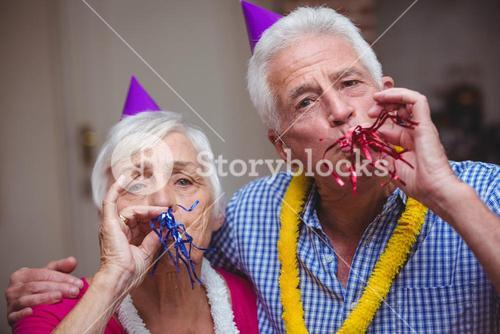 Portrait of senior couple blowing party horn