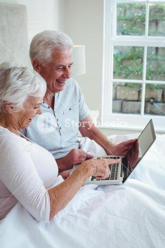 Happy retired couple with laptop
