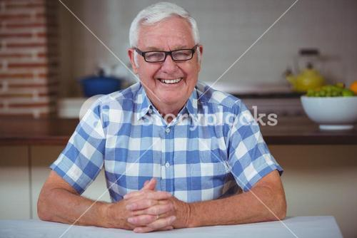 Portrait of smiling senior man with hands clasped