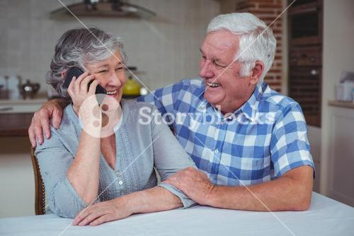 Senior woman talking on mobile phone while sitting with husband