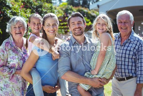 Portrait of happy family standing in back yard
