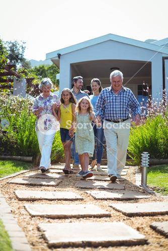 Laughing multi-generation family walking on footpath
