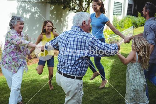 Multi-generation family playing in back yard