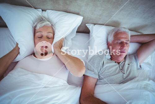 Senior woman blocking ears with pillow while husband snoring on bed
