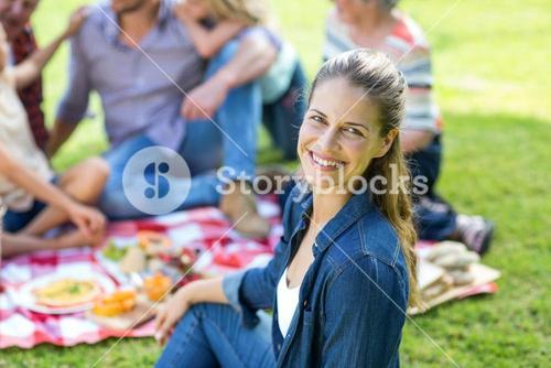 Young woman sitting with family in background at back yard