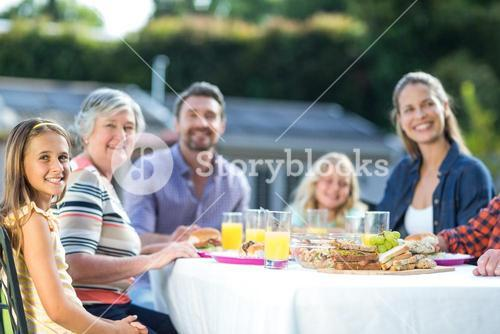Happy girl sitting with family at table