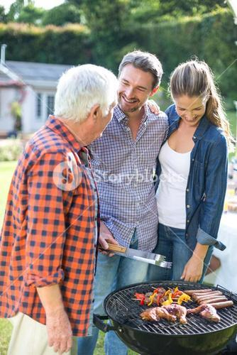 Couple with senior man preparing food on barbecue