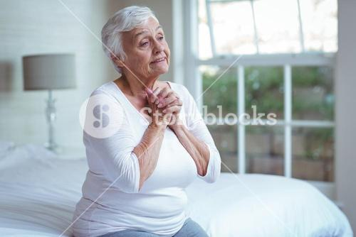 Senior woman joining hands on bed