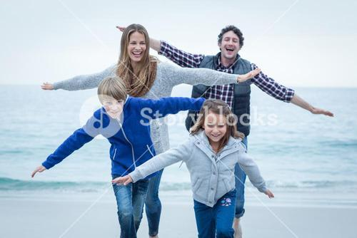 Children enjoying with parents at sea shore