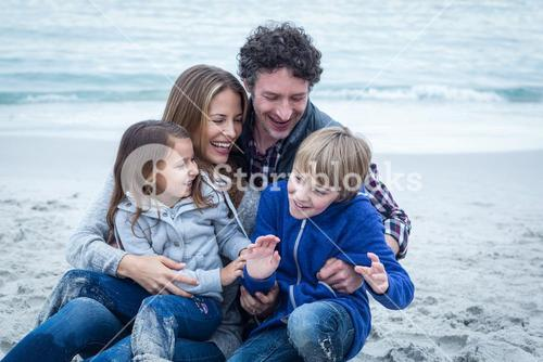 Cheerful parents with children at sea shore