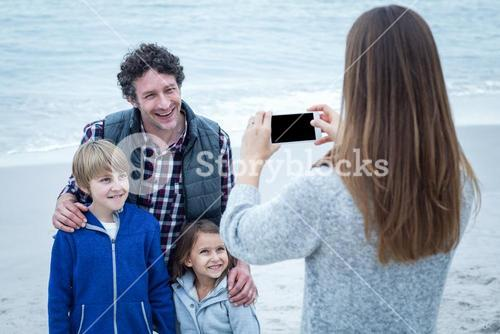 Mother photographing family at beach