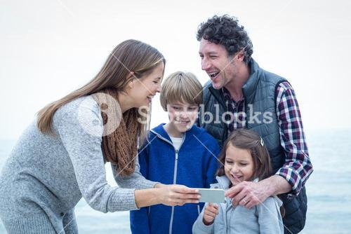 Cheerful family with mobile phone at beach