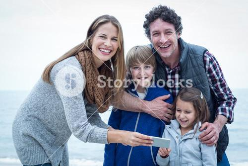 Cheerful family with mobile phone enjoying at beach
