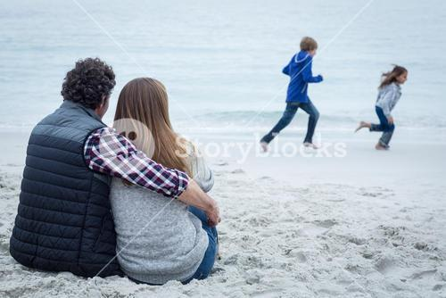 Couple sitting while children playing at sea shore