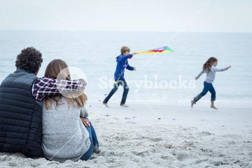 Couple sitting while playful children at sea shore