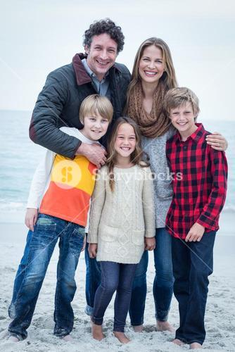 Portrait of cheerful family standing at sea shore