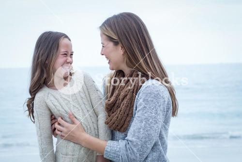 Cheerful mother and daughter at sea shore