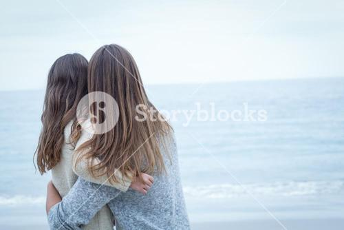 Mother embracing daughter at sea shore